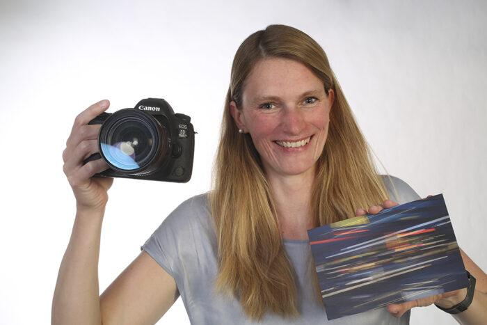 Adina Kagermaier hält in der rechten Hand ihre Kamera und in der linken Hand hält sie ein kleines Kunstwerk, welches sie selbst kreiert hat.