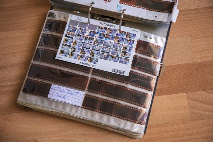 Ein aufgeklappter DIN A4 Ordner, voll mit Aufbewahrungshüllen für Negative. Zu sehen ist ein Film mit dem passenden Index für die Übersichtlichkeit.